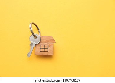 Key with trinket in shape of house on color background