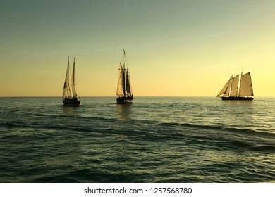 Key West, FL – March 11, 2017: Sunset skies in blue and gold tones provide the background for three tall ships sailing on the dark gulf waters to capture the sunset, a daily tourist event in Key West.