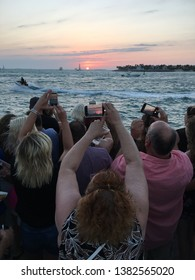 Key West Fl, USA March 20, 2018 People hoist their cameras over their heads, looking to get a shot of the sun before it dips below the horizon in Key West, Florida