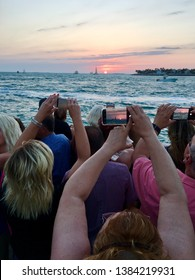 Key West Fl, USA March 20, 2018 Arms and phones are raised as tourists attempt to capture the last of the sun as it dips below the horizon in Key West, Florida