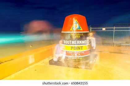KEY WEST, FLORIDA - JANUARY 12, 2016: Tourists take photographs at night in Southernmost Point. Key West is a famous tourist attraction in Florida.