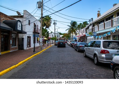 """Key West, Florida - May 2019: A view down brick paved Fitzpatrick St, Key West in front of Hog's Breath Clothing."""