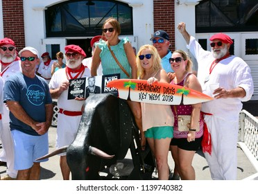 KEY WEST, FLORIDA, USA, JULY 21:  Hemingway Days Festival in Old Town Key West, Florida, on July 21, 2018.  Tourists have their pictures taken on a bull with Ernest Hemingway look alikes.