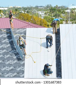 KEY WEST, FLORIDA, USA-JANUARY 31, 2019:  A roofing crew repairs damage to a tin roof caused by Hurricane Irma in Key West, Florida, on Thursday, January 31, 2019.