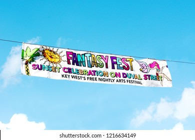 KEY WEST, FLORIDA, USA-OCTOBER 26, 2018:  A colorful  Key West Fantasy Fest Sunset Celebration banner, hanging against a blue sky with white clouds, on Friday, October 26, 2018.