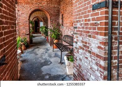 Key West, USA - May 1, 2018: Brick sidewalk corridor path entrance to Martello Botanical Garden Center with nobody, architecture in Florida