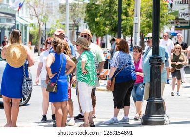 Key West, USA - May 1, 2018: Group of elder, senior, old tourists standing, waiting at traffic light crosswalk, crossing at Duval street road, sidewalk, people walking in summer, Florida keys city
