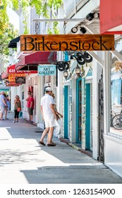 Key West, USA - May 1, 2018: Restaurants, cafe, Guild hall art gallery studio, stores, Birkenstock shoes shop, store on Duval street road, people, tourists walking on sidewalk in summer, Florida city