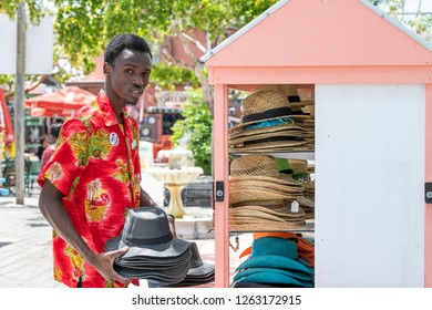 Key West, USA - May 1, 2018: Duval street Mallory Square outdoor shopping mall, market, salesperson, African American young man, seller, vendor selling, stacking arranging straw hats in Florida city