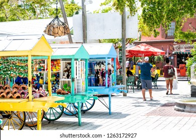 Key West, USA - May 1, 2018: Duval street Mallory Square outdoor shopping mall, market, people walking, buying souvenirs, in summer Florida city, multicolored stands, booth, kiosk selling toys