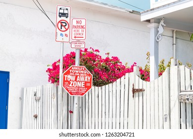 Key West, USA - May 1, 2018: No parking here to corner, tow away zone traffic, road sign at bus stop in Florida keys on sidewalk with house, building in background outside, outdoors