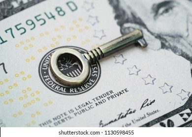 Key for world and United States economy, FED consider interest rate hike, important bronze mini key on US Federal Reserve emblem on dollars banknote.