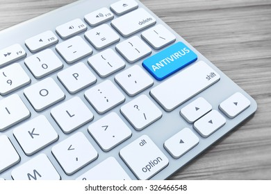Keyboard with antivirus button on wooden background