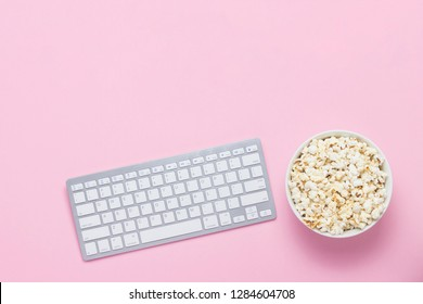 Keyboard and bowl of popcorn on a pink background. The concept of watching movies, TV shows and shows online. Flat lay, top view.