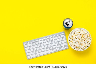 Keyboard, can of drink and a bowl of popcorn on a yellow background. The concept of watching movies, TV shows, shows, sports online. Flat lay, top view.