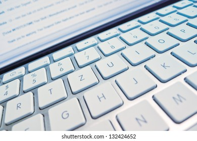 the keyboard of a computer in front of a screen. computer and internet