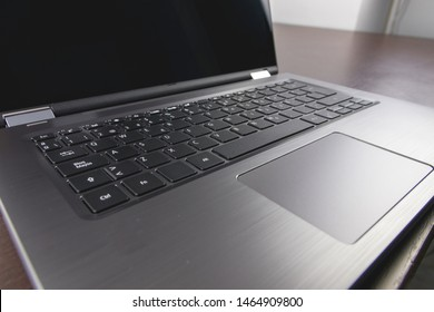 Keyboard of a foldable 2-in-1 laptop, where you can see the screen, the keyboard and the touchpad of the computer