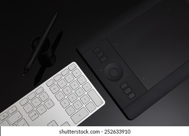 Keyboard and a graphic tablet on a black desk.