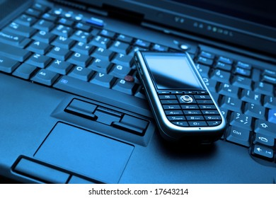 Keyboard of high-end laptop and modern smartphone on it. RAW and Tiff also available on demand. Blue-toned photo.