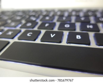 keyboard layout backlit illuminated with black keys, white characters and blue light. Blurred effect