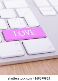 A keyboard with the letters �Love� on a pink key