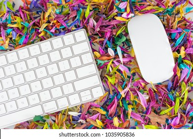 A keyboard and mouse against a background of colorful flower petals.