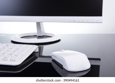 Keyboard and mouse design on a black desk and a monitor in the background