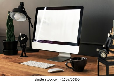 Keyboard, mouse and desktop computer on wooden desk with lamp in work area interior. Real photo. Paste your text here
