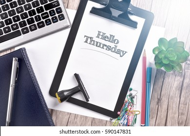 Keyboard with notebook and clipboard on wooden table with text HELLO THURSDAY