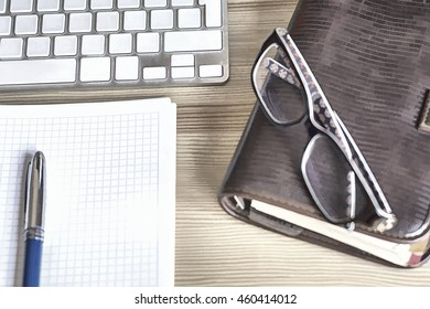 Keyboard and office supplies on the wooden table. Cartoon