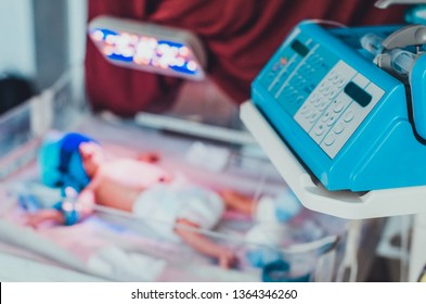 A keyboard on an infant warmer and a baby in it at the blurred background. Concept of children medical treatment. Medical equipment