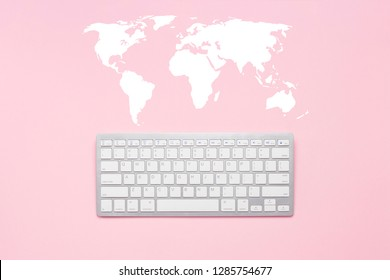 Keyboard on a pink background. World map. Concept global network, communication with the world, anywhere in the world. Flat lay, top view.