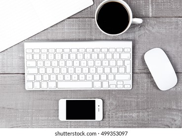 Keyboard with phone coffee cup and mouse on office desk