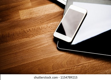 keyboard with phone and tablet pc on wooden desk