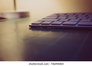 Keyboard sitting on a cutting matt with light in the background closeup