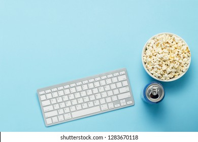 Keyboard and tin can with a drink, energy drink, a bowl of popcorn on a blue background. The concept of watching movies, TV shows, sports events online. Flat lay, top view.