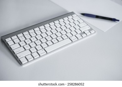Keyboard with white paper and pen