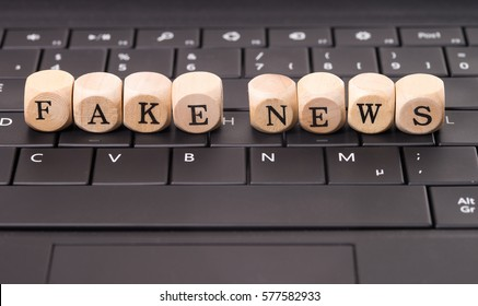 Keyboard and wooden cube with the words Fake News