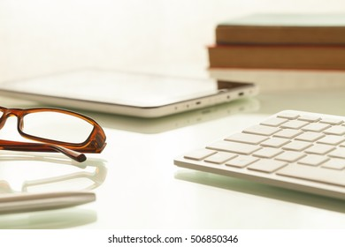 keyboard,tablet and glasses over office table