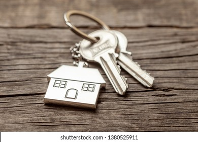 Keychain house with keys on old wooden boards