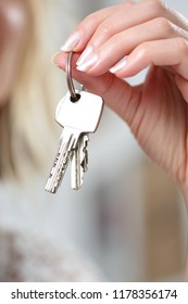 A Keychain with various keys in a womans hand