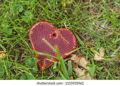 Keychain-reflector for keys in the form of a heart on the grass.