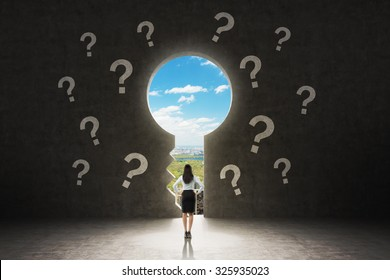 A keyhole in the concrete wall. A business lady dressed in formal suit is looking at New York City in the hole. There are drawn question marks around the hole.