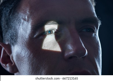keyhole light on eye of man as symbol for observation and voyeurism