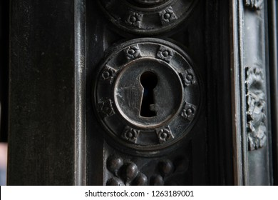Keyhole on an ancient architectural door of an old church. The brass handle looks  stunning along with the black wooden architecture, revealing medieval style.
