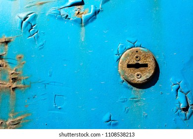 Keyhole on the car door. Rusty metal. Detail of the car. Blue color.