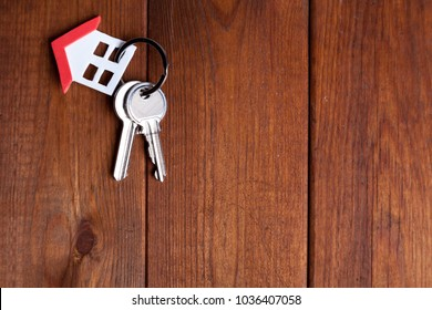 Keyring of small house with red roof over brown wood.