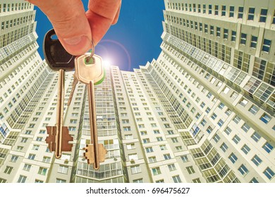 The keys to the apartment in the background of the facade of the house . ?he concept of sales in the real estate market .