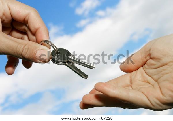 keys being handed over against blue sky