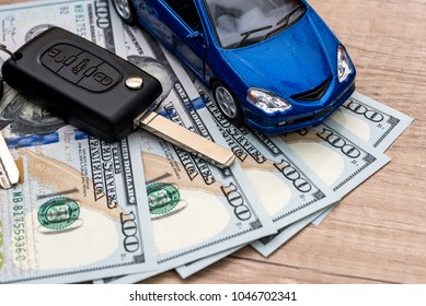 Keys to the car, dollars and the car that lie on the desk